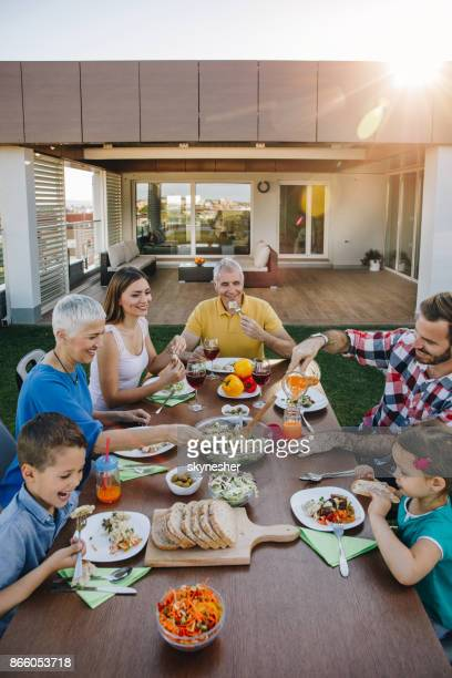 happy multi-generation family enjoying in lunch time on a penthouse patio. - penthouse girls stock pictures, royalty-free photos & images