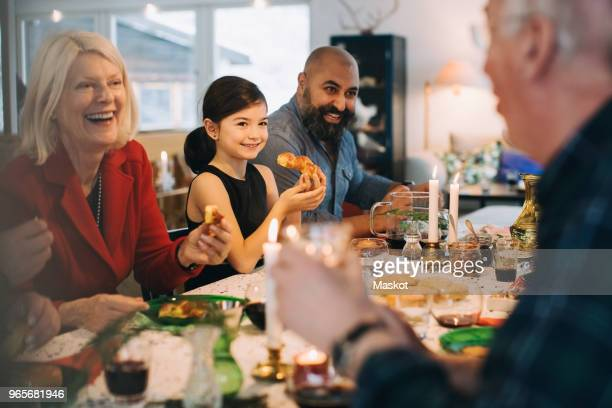 happy multi-generation family enjoying meal at table during christmas - person gemischter abstammung stock-fotos und bilder