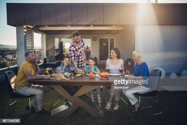 happy multi-generation family having a meal on a penthouse balcony. - penthouse girls stock pictures, royalty-free photos & images