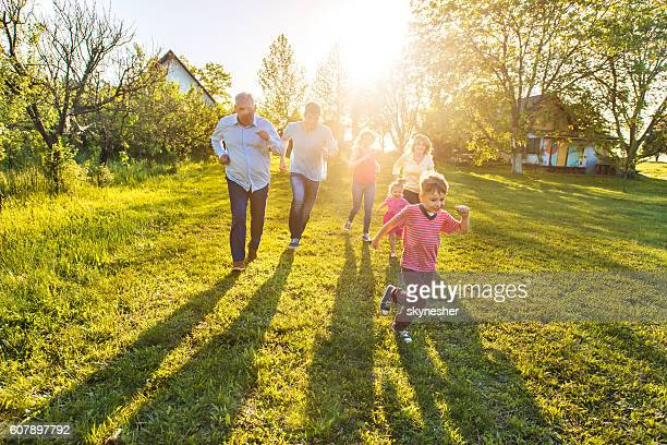 Happy multi-generation family having fun and running on the grass.