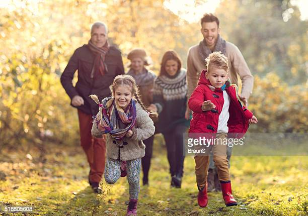 Happy multi-generation family having fun in the park while chasi