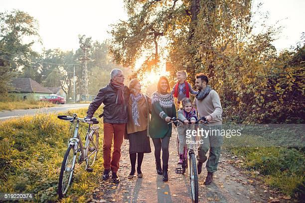 Happy multi-generation family having fun with bikes in autumn da