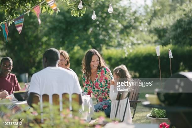 happy multi-generation family having lunch together at patio during garden party - middelgrote groep mensen stockfoto's en -beelden