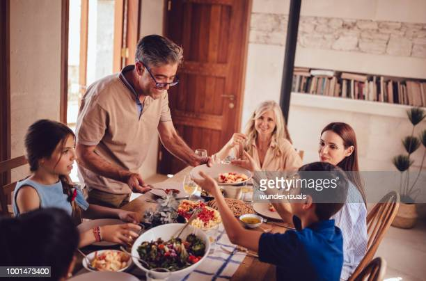 happy multi-generation family having lunch with grandfather serving food - tradition stock pictures, royalty-free photos & images