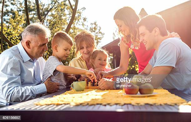 happy multi-generation family playing chess in the garden. - game board stock photos and pictures