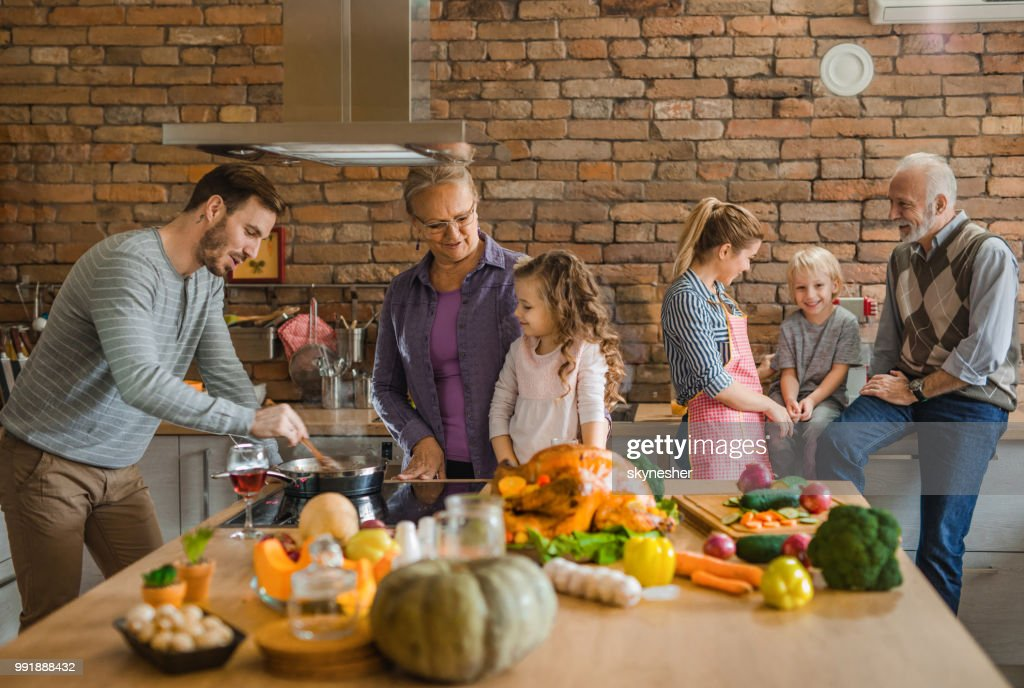 Happy multi-generation family preparing Thanksgiving dinner in the kitchen. : Stock Photo