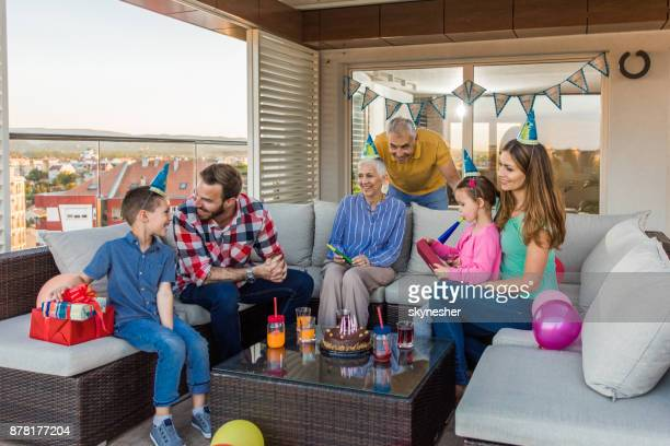 happy multi-generation family relaxing at penthouse terrace while having a birthday party. - penthouse girls stock pictures, royalty-free photos & images