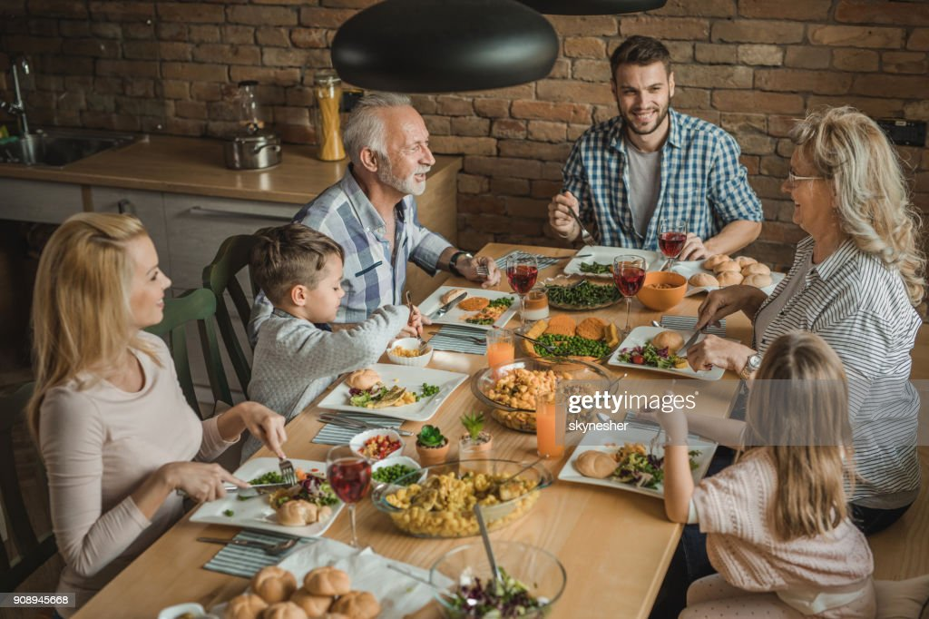 Happy multi-generation family sitting at dining table and talking during lunch time. : Stock Photo