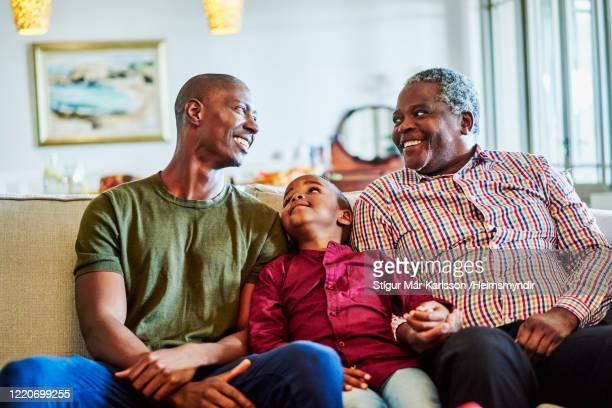 happy multi-generation family sitting on sofa - generation gap stock pictures, royalty-free photos & images