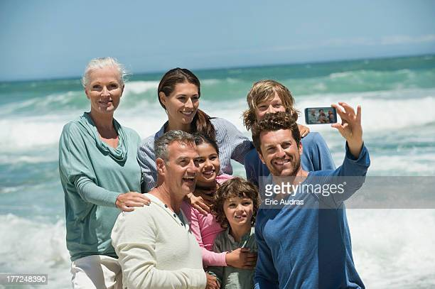 happy multi-generation family taking a self portrait with a cell phone on the beach - medium group of people stock pictures, royalty-free photos & images