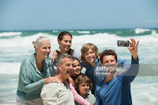 Happy multi-generation family taking a self portrait with a cell phone on the beach