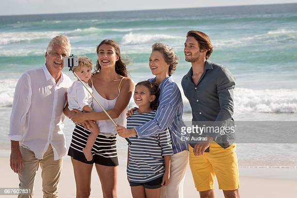 Happy multi-generation family taking selfie together on beach