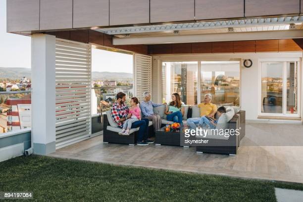 happy multi-generation family talking while relaxing on a penthouse patio. - penthouse girls stock pictures, royalty-free photos & images