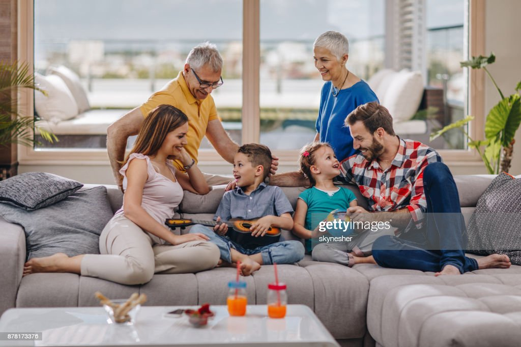 Happy multi-generation family talking while spending a day together at home. : Stock Photo