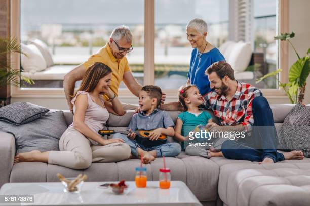 happy multi-generation family talking while spending a day together at home. - penthouse girls stock pictures, royalty-free photos & images
