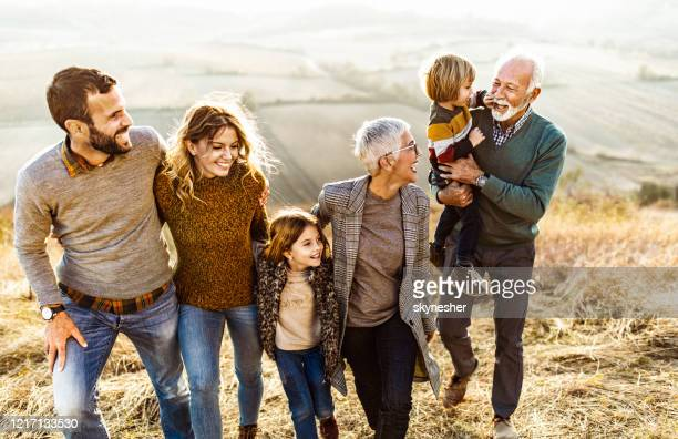 happy multi-generation family talking while taking a walk on the field. - multi generation family stock pictures, royalty-free photos & images