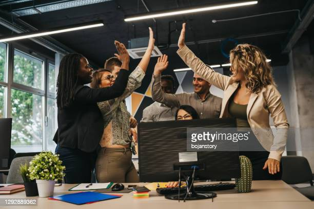 happy multinational coworkers giving high five celebrating great teamwork result - award stock pictures, royalty-free photos & images