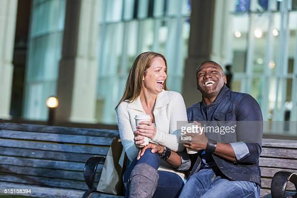 Multiraciale heureux couple assis sur un banc avec café