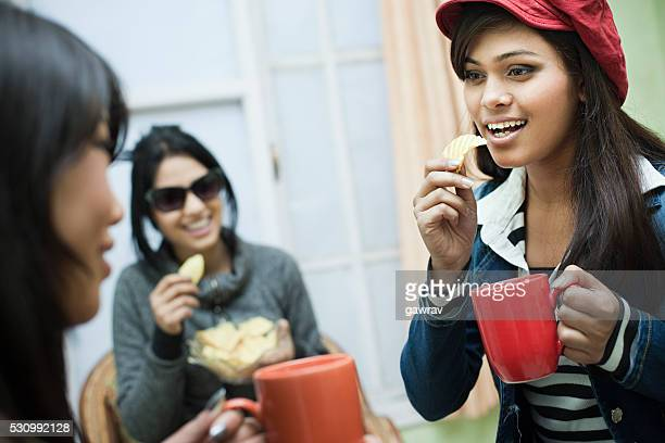 Happy multiracial group of female friends enjoying coffee with snacks.