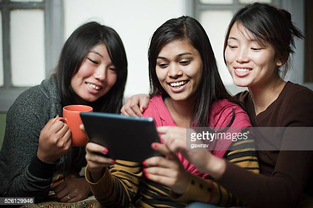 Happy multiracial group of female friends sharing digital tablet.