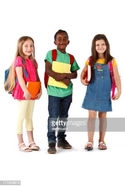 Multirazziale felice scuola bambini in piedi con i libri e zaini