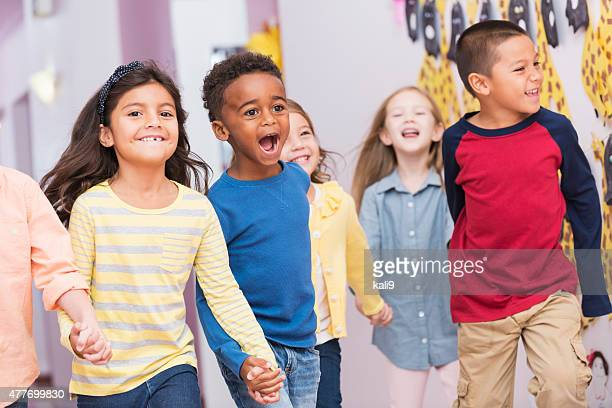 Happy multiracial school children walking thru hallway