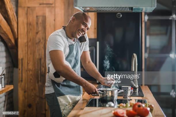 multi-tasking afroamericano hombre feliz hablando por teléfono móvil mientras se cocina en la cocina. - black cook fotografías e imágenes de stock