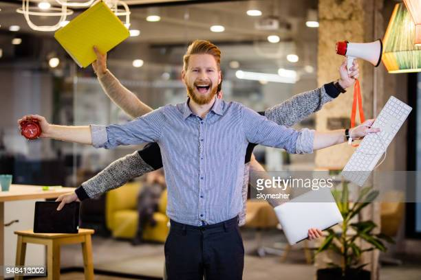 happy multi-tasking businessman with many hands in the office. - efficiency stock pictures, royalty-free photos & images