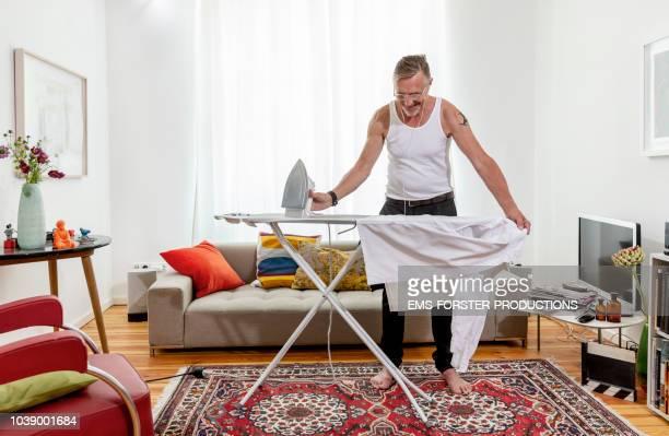 Happy, multi-tasking senior ironing his shirt in living room at home.