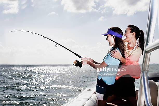 happy mum and daughter fishing on motor boat