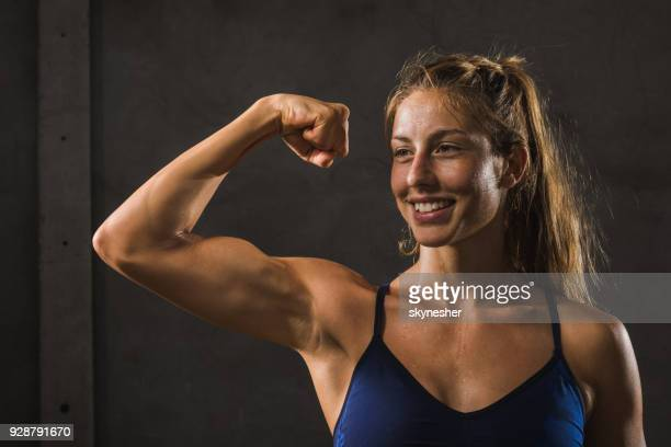 happy muscular build woman flexing her bicep against gray wall. - flexing muscles stock pictures, royalty-free photos & images