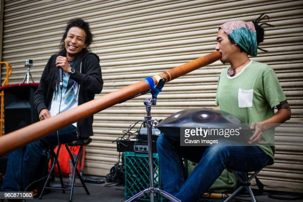 happy musicians playing instruments during event - steel drum - fotografias e filmes do acervo