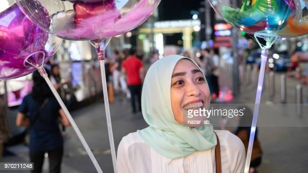 Happy Muslim Woman Holding Balloons.