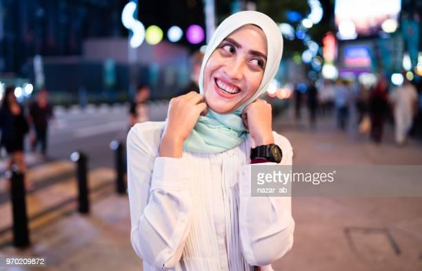 Happy Muslim woman in market.