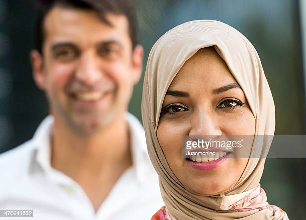 Happy Muslim woman with man in soft focus.