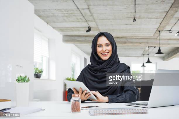 Happy muslim woman working in the office