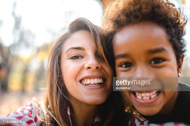 happy nanny and black girl taking a self portrait photography n nature. - adoption stock pictures, royalty-free photos & images