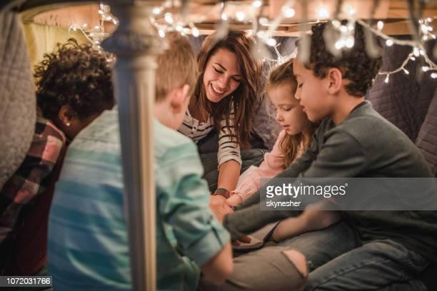 ama feliz se divertindo com crianças pequenas em uma barraca em casa. - dama de companhia - fotografias e filmes do acervo