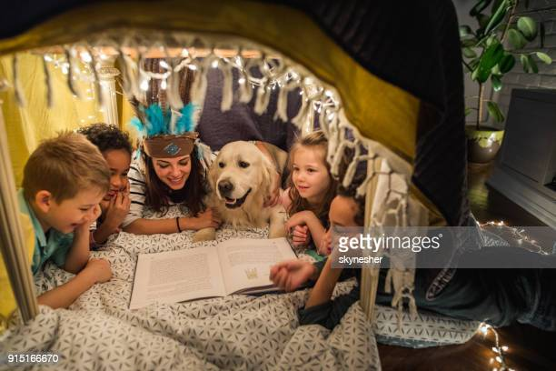 Nanny feliz leyendo un libro para niños pequeños y un perro en una tienda de campaña.