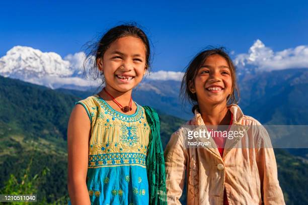 happy nepalese little girls, annapurna range on background - annapurna south stock pictures, royalty-free photos & images
