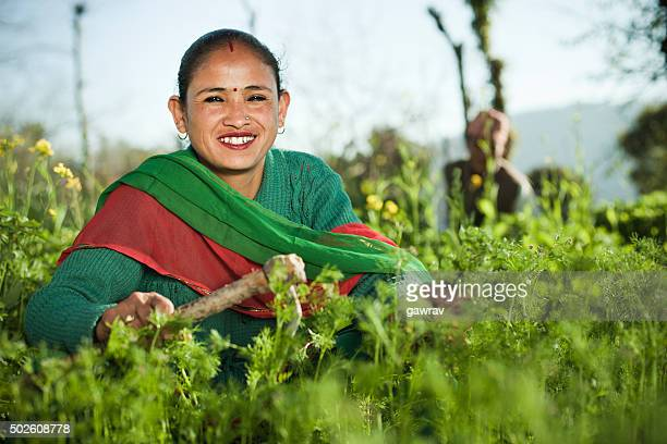 Happy Nepalese peasant woman working in farm.