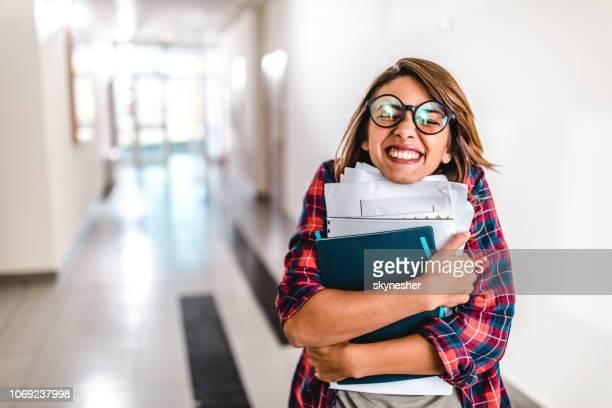 gelukkig nerdy student met boeken in een hal van de school. - studeren stockfoto's en -beelden