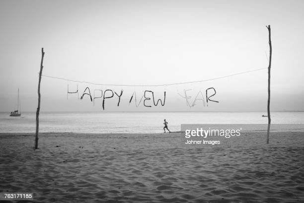 Happy New Year text on beach