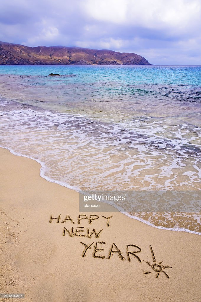 happy new year written in the sand on a beach stock photo