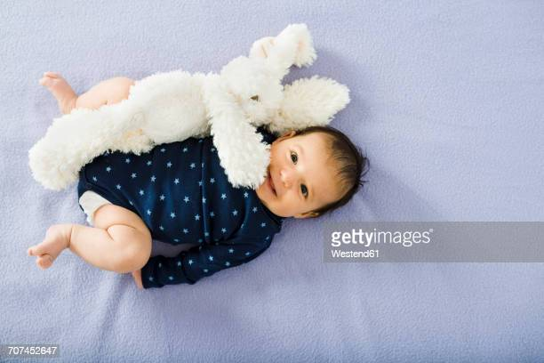 Happy newborn baby girl on bed with a stuffed rabbit