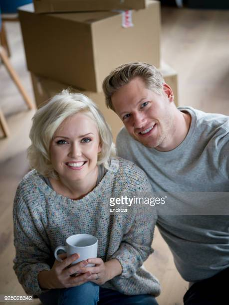 Heureux couple nouvellement mer prendre une pause de se déplacer dans leur nouvelle maison regardant sourire caméra