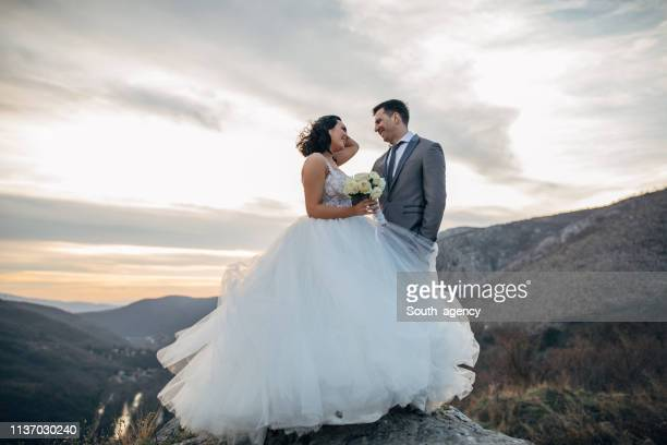 happy newlywed couple on mountain - wedding dress stock pictures, royalty-free photos & images