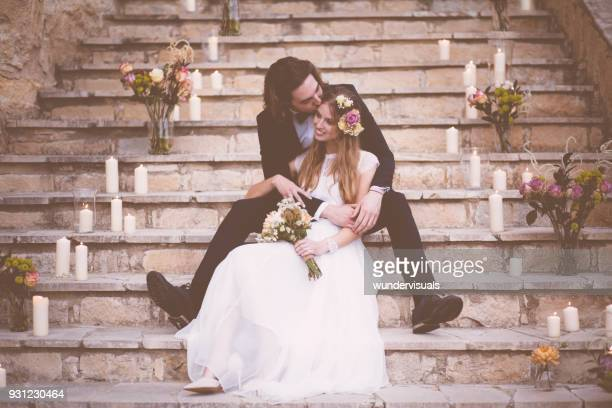Happy newlywed couple sitting on stone steps embracing and kissing