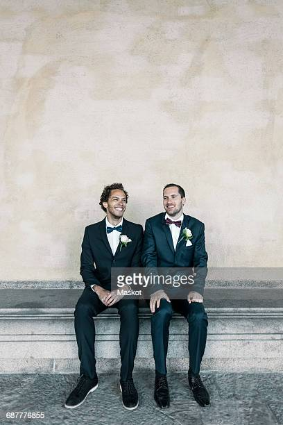 Happy newlywed gay couple sitting on bench against wall