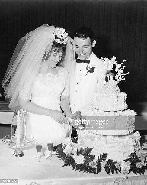 Happy newlyweds cutting wedding cake